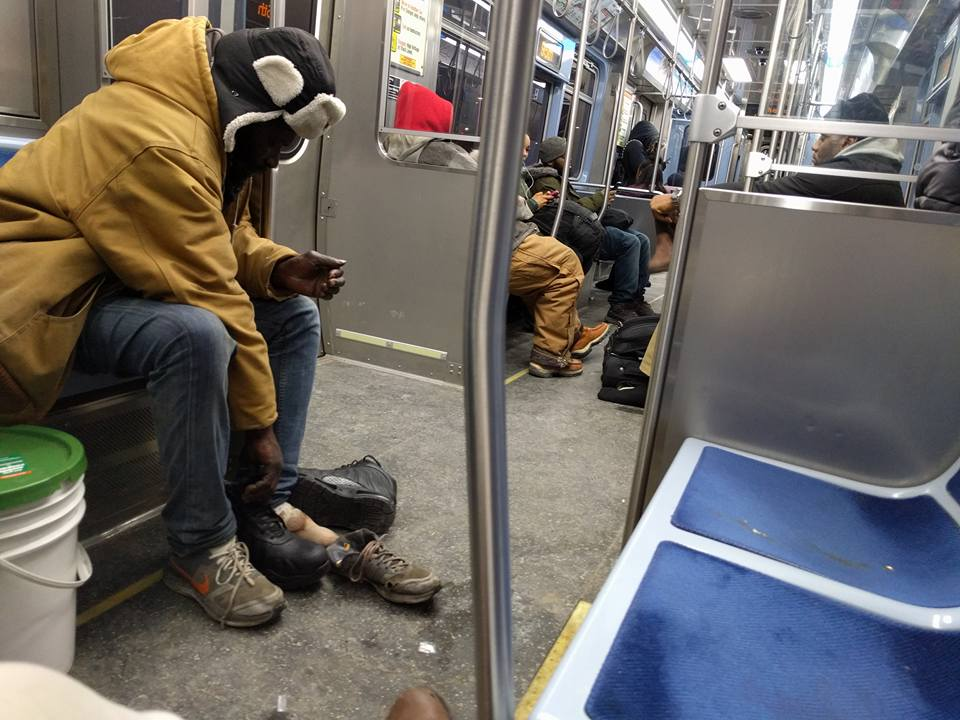 Young man gives homeless man on a CTA Red Line train the boots off his own feet.